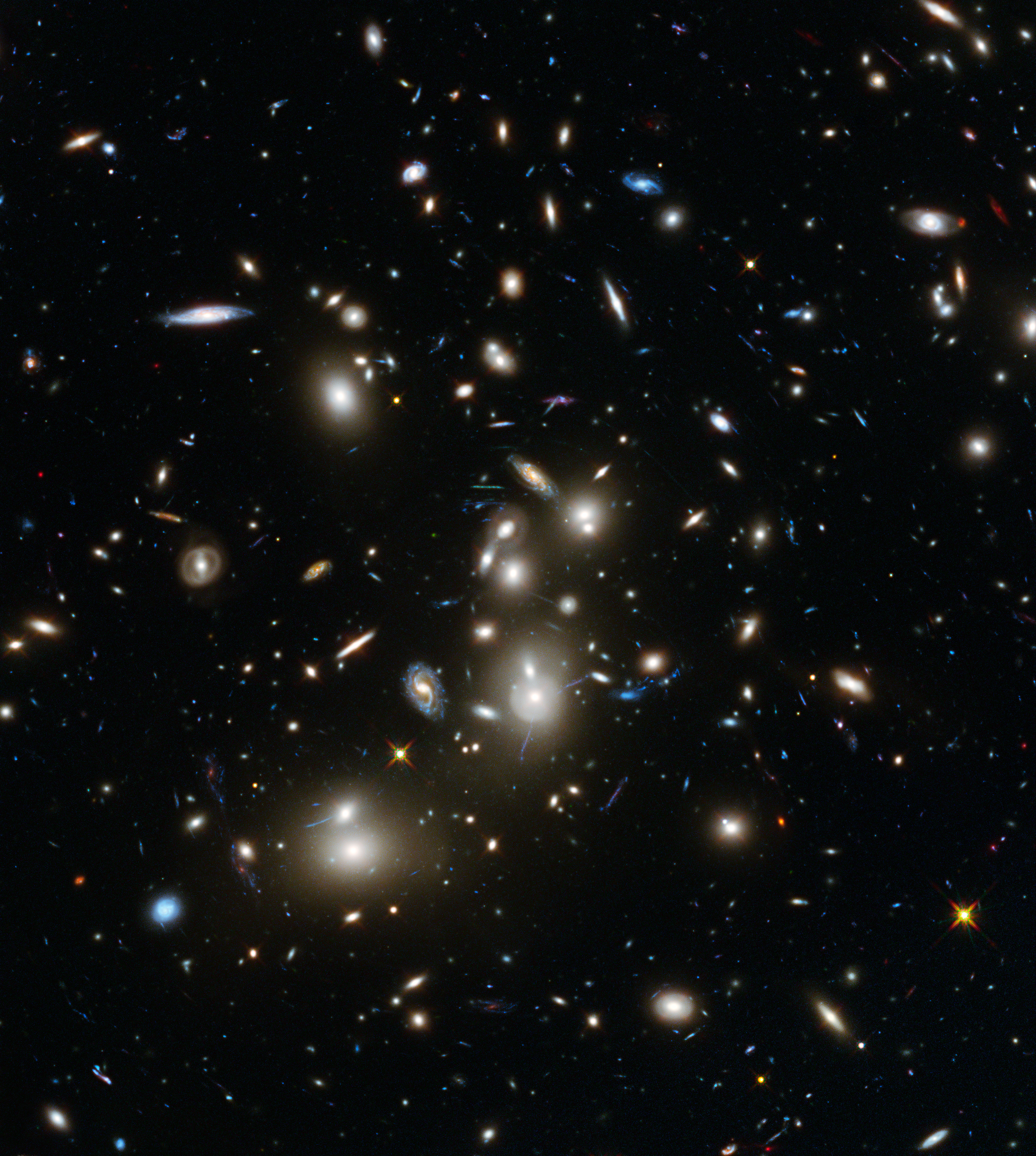 This image of Abell 2744 is the first to come from Hubble's Frontier Fields observing programme, which is using the magnifying power of enormous galaxy clusters to peer deep into the distant Universe. Abell 2744, nicknamed Pandora's Cluster, is thought to have a very violent history, having formed from a cosmic pile-up of multiple galaxy clusters. Abell 2744 is the first of six targets for an observing programme known as Frontier Fields. This three-year, 840-orbit programme will yield our deepest views of the Universe to date, using the power of Hubble to explore more distant regions of space than could otherwise be seen, by observing gravitational lensing effects around six different galaxy clusters.